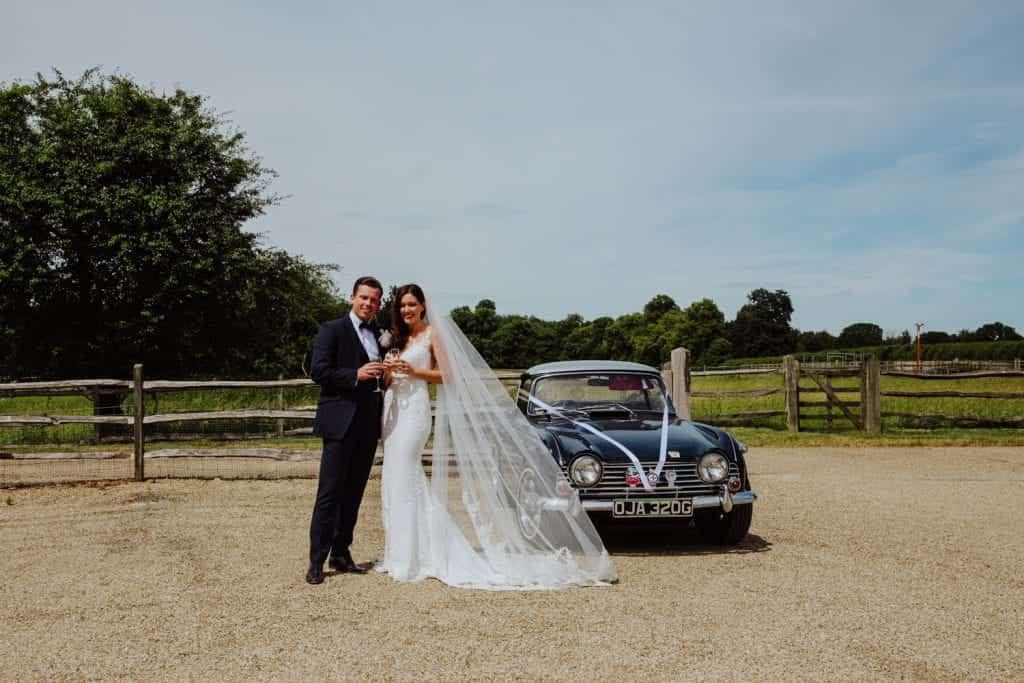 bride and groom at gayness park with vintage car