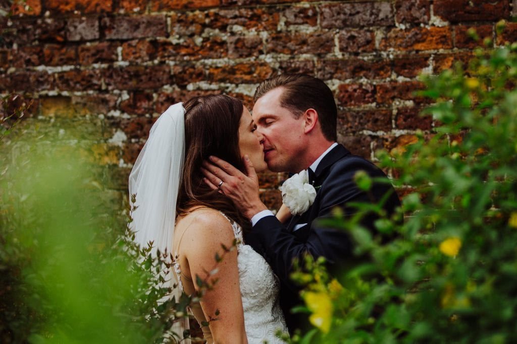 bride and groom at gayness park by the red brick wall - gaynes park