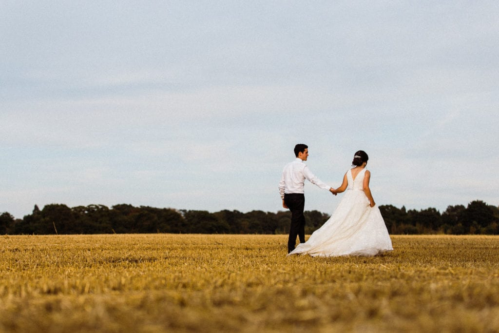 bride and groom walking through a field - picture taken by a wedding photographer in Essex