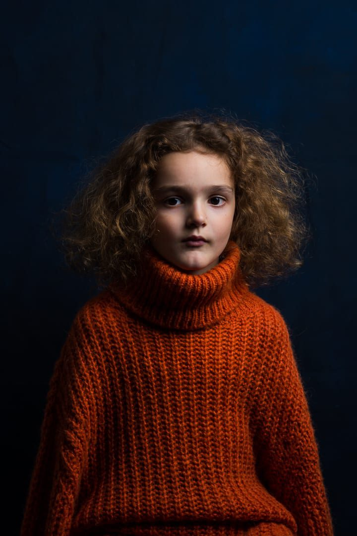 young boy with orange chunky knitted jumper