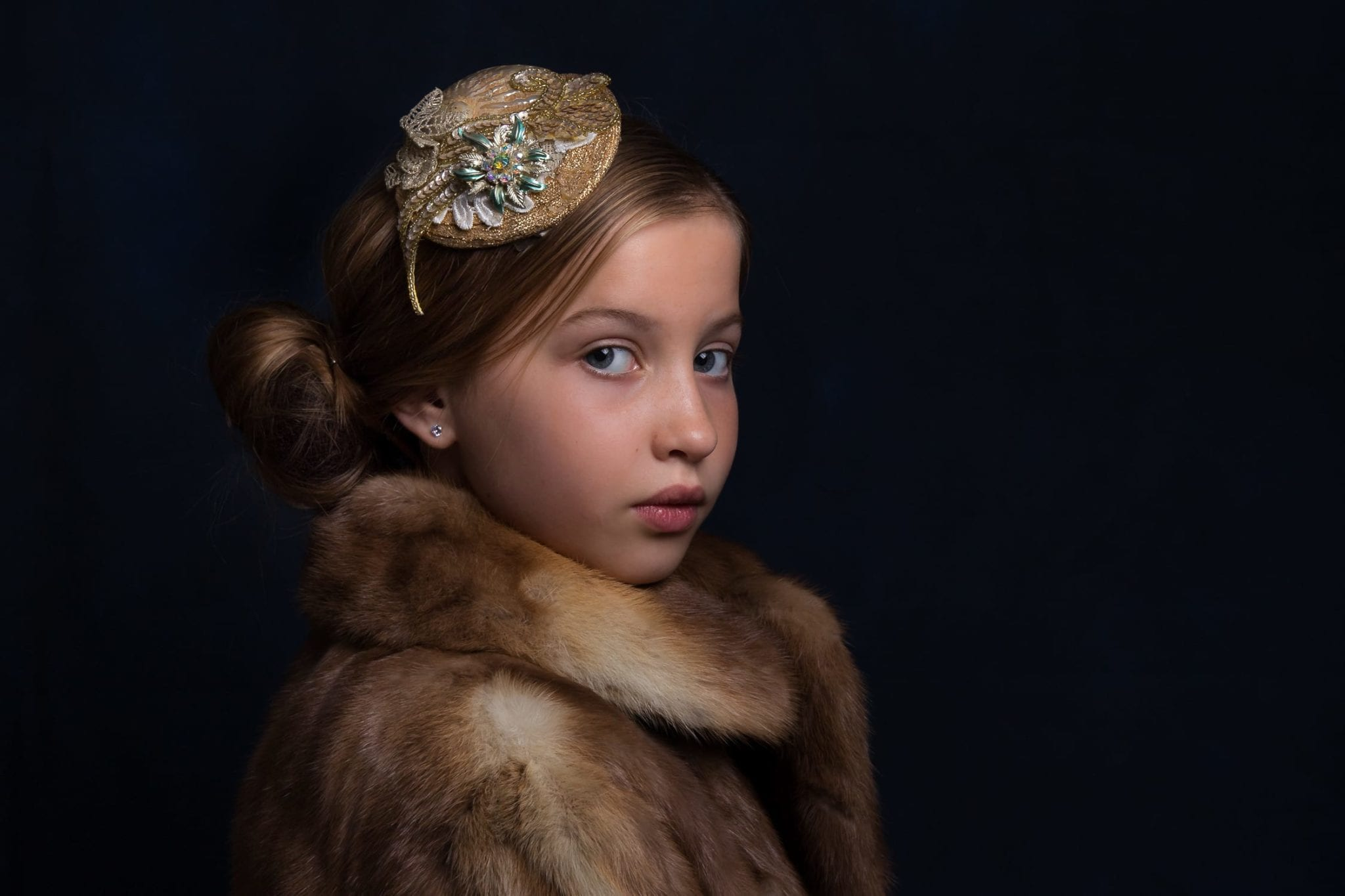young girl dressed in fur coat and hair pice image taken in a chelmsford family photography studio