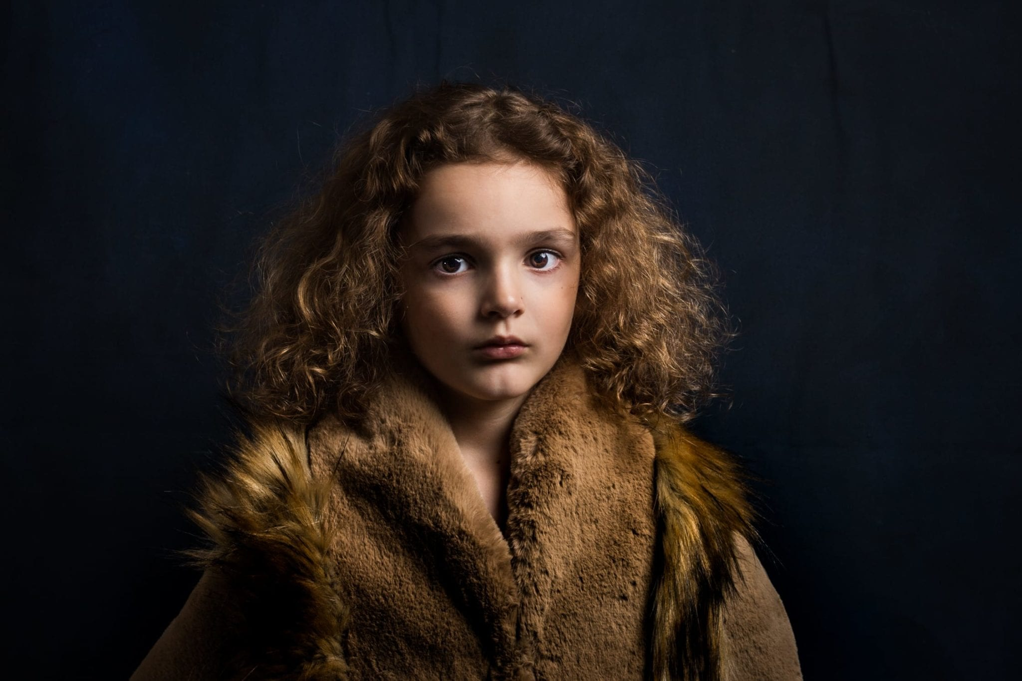 boy with long curly hair in brown fur coat taken in family photography Chelmsford